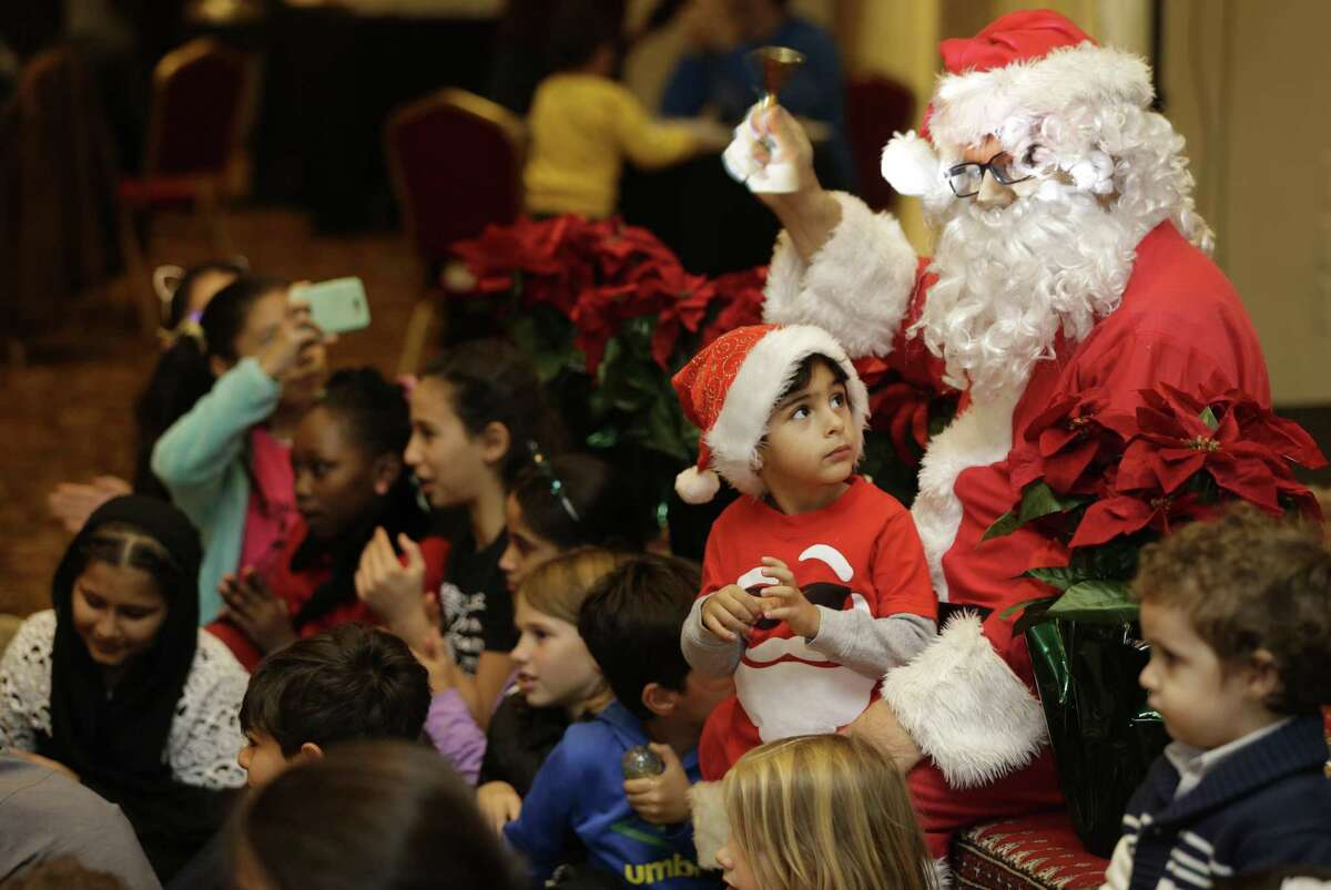 Anthony Nasr, 3, sits on the lap of Baba Noël (Santa) as a group of children sing Christmas Carols in Arabic and English during the Christmas In the Middle East: Mediterranean Brunch with Baba Noël at the Arab American Cultural & Community Center, 10555 Stancliff Rd., Saturday, Dec. 8, 2018, in Houston.