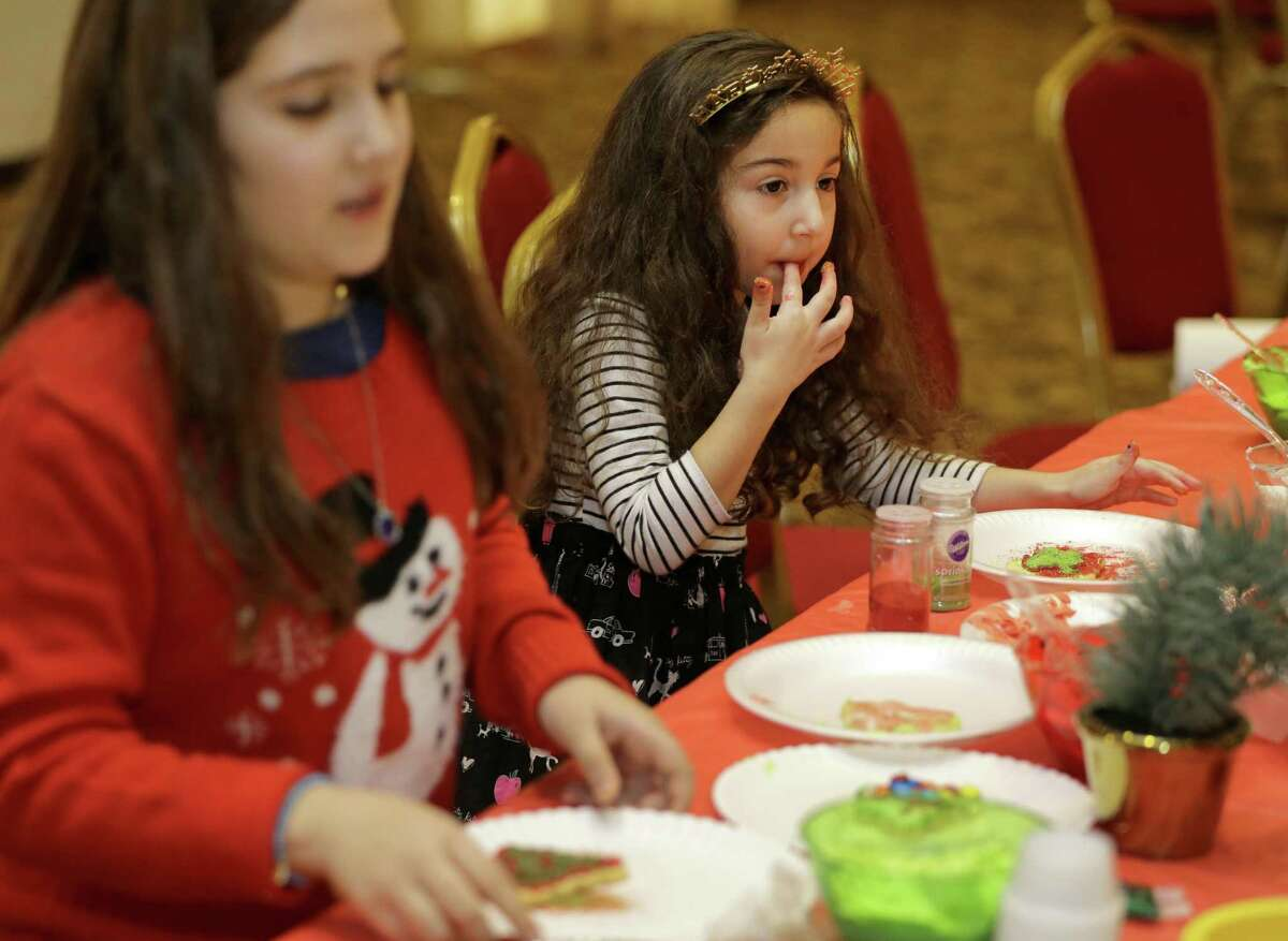 Sara Patel, 9, left, and her cousin, Violet Prontka, 4, right, decorate cookies during the Christmas In the Middle East: Mediterranean Brunch with Baba Noël at the Arab American Cultural & Community Center, 10555 Stancliff Rd., Saturday, Dec. 8, 2018, in Houston. Other activities included ornament decorating, pictures with with Baba Noël (Santa) and singing Christmas Carols in Arabic and English.