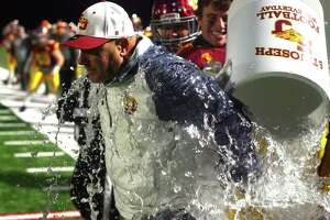 St. Joseph players give head coach Joe DellaVecchia a celebratory water-cooler shower after beating Berlin in Class M state championship on Saturday in Shelton.