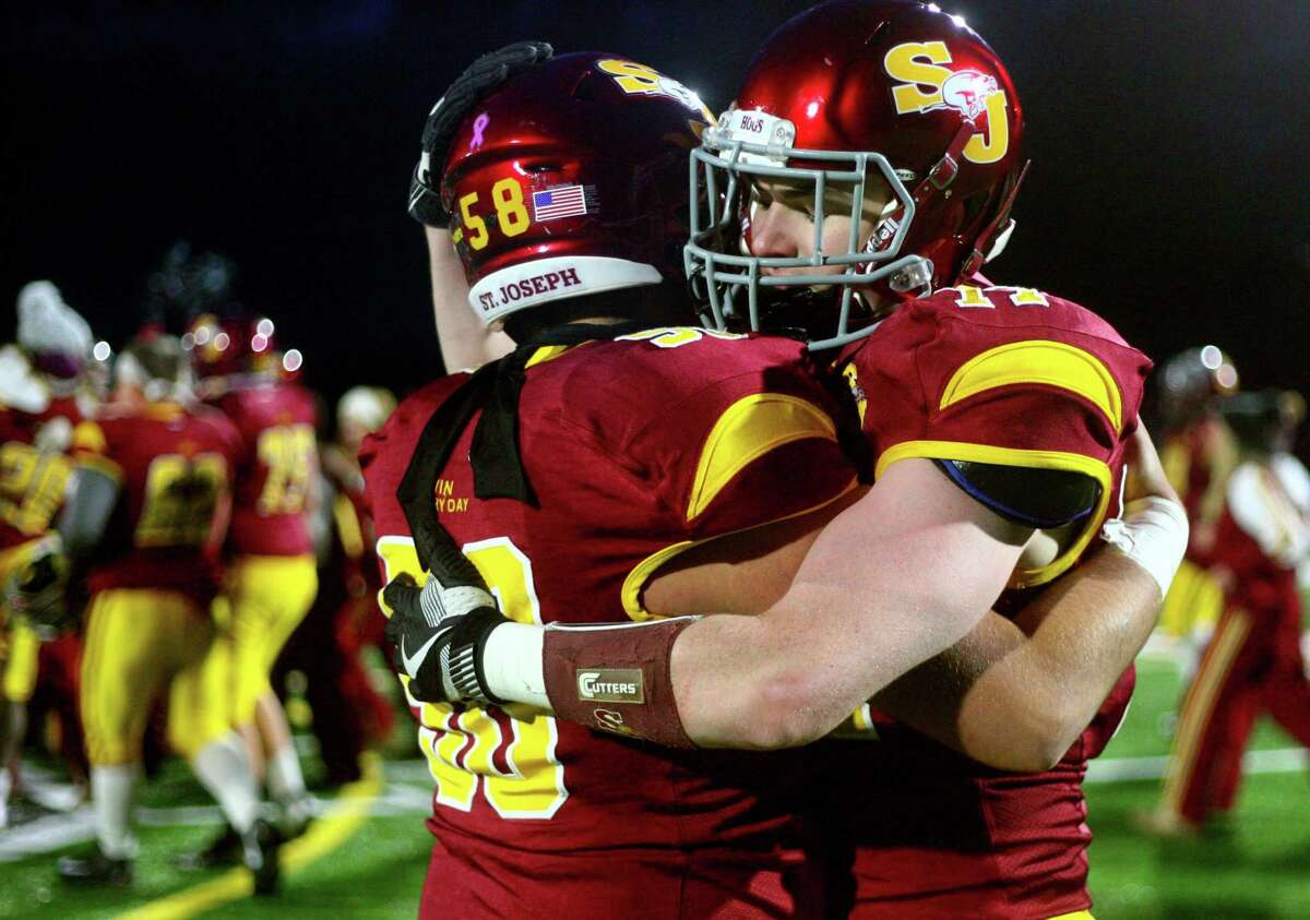 St. Joseph players Dennis Elrod (58), at left, and Karl Kelly (77) hug each other after the team beat Berlin during Class M state championship football action in Shelton, Conn., on Saturday Dec. 8, 2018.