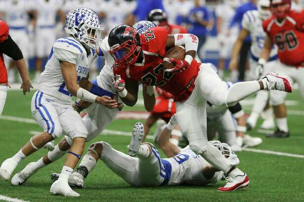 Wagner's L. J. Butler (22) powers his way for yardage against Mission Veterans Memorial's Elias Delgado (27) in the first half in the Region IV-5A Division II final game at the Alamodome on Saturday, Dec. 8, 2018. (Kin Man Hui/San Antonio Express-News)