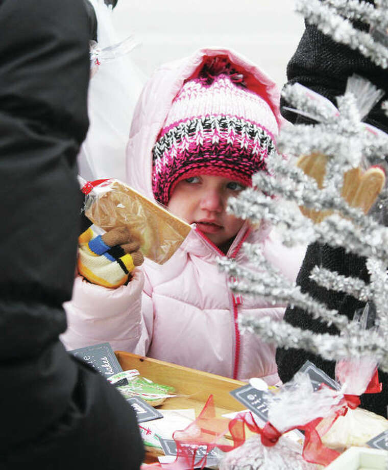 A bundled-up Lylah Blurton, 4, of Greenville, hands over an item she is purchasing at the Edwardsville Winter Market Saturday. Customers braved temperatures in the mid- to lower-20s to shop for a variety of goods. The market is sponsored by the Edwardsville Parks and Recreation Department. Photo: Scott Cousins | The Telegraph