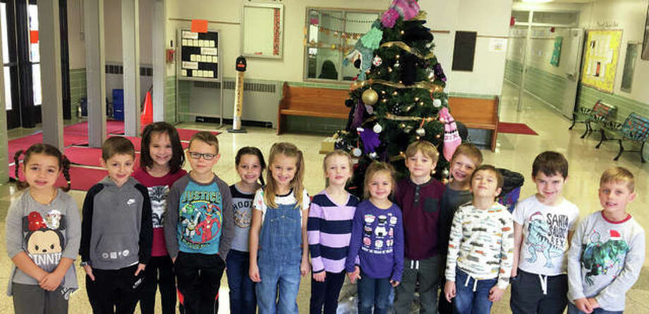 Students at Leclaire Elementary pose in front of the school's Giving Tree Friday. The school, located at 801 Franklin Ave., is currently collecting hats and gloves for children in need. In addition to the hat and mitten tree, Leclaire students also participated in the United Way's Community Christmas collection and are performing random acts of kindness for the month of December. Leclaire Elementary Principal Dr. Cornelia Smith and school staff said the activities emphasize kindness and giving, especially this time of the year. Photo: Submitted For The Intelligencer