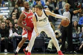 Dallas Mavericks forward Luka Doncic (77) backs down Houston Rockets guard Chris Paul (3) during the first half of an NBA basketball game, Saturday, Dec. 8, 2018, in Dallas. (AP Photo/Cooper Neill)
