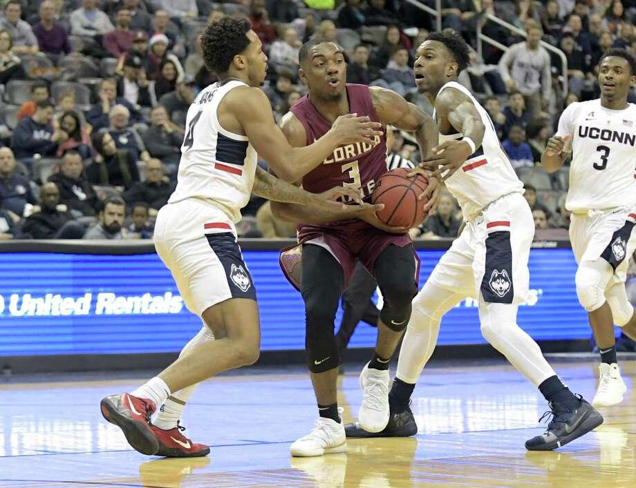 Florida State's Trent Forrest (3) attempts to split the defense of UConn's Jalen Adams, left, and Tarin Smith on Saturday. Photo: Bill Kostroun / Associated Press / Copyright 2018 The Associated Press. All rights reserved