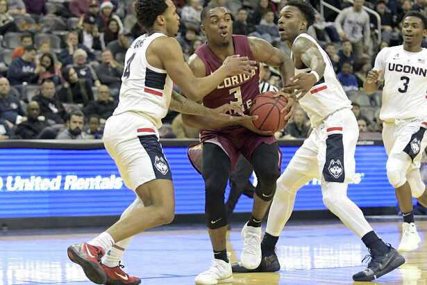 Florida State's Trent Forrest (3) attempts to split the defense of UConn's Jalen Adams, left, and Tarin Smith on Saturday.