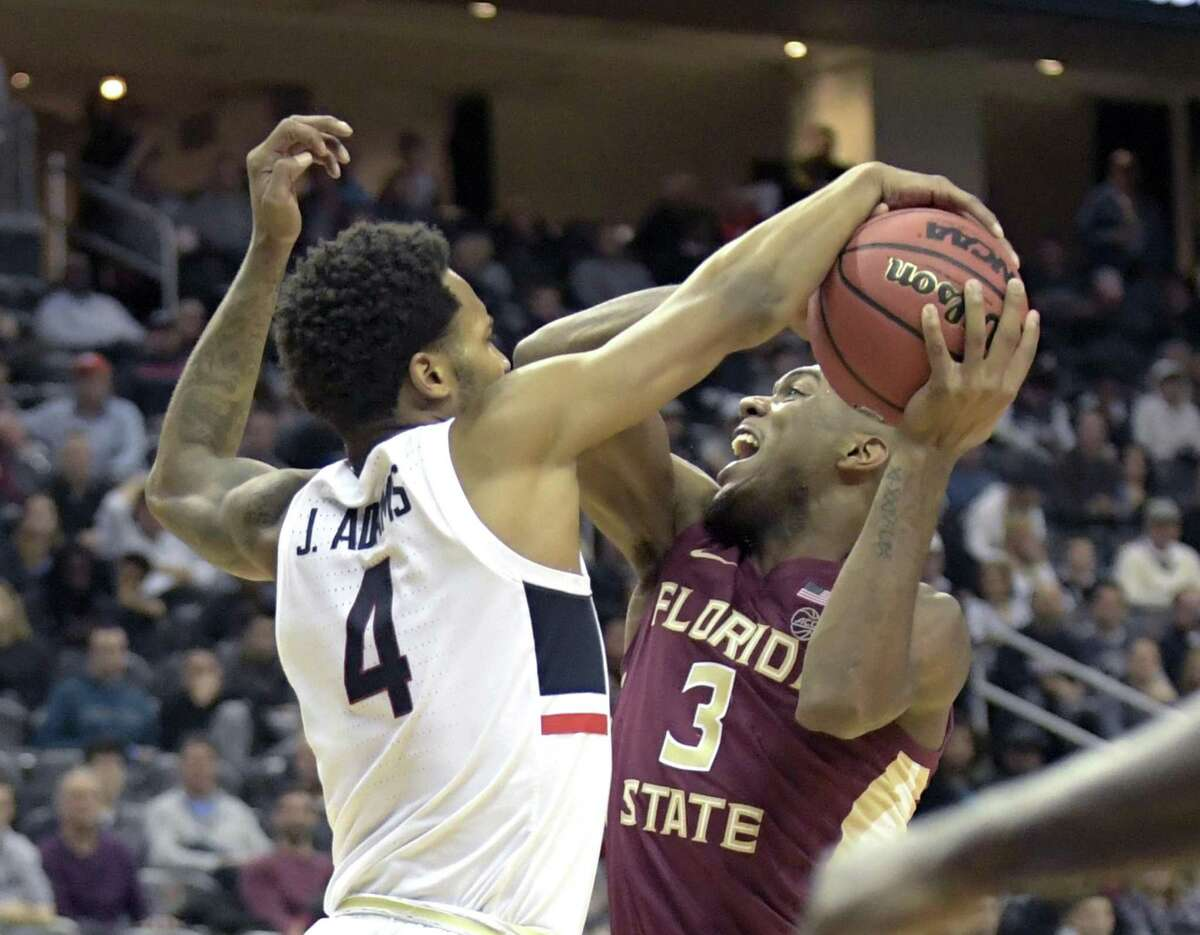 Florida State's Trent Forrest (3) is tied up by UConn's Jalen Adams on Saturday.
