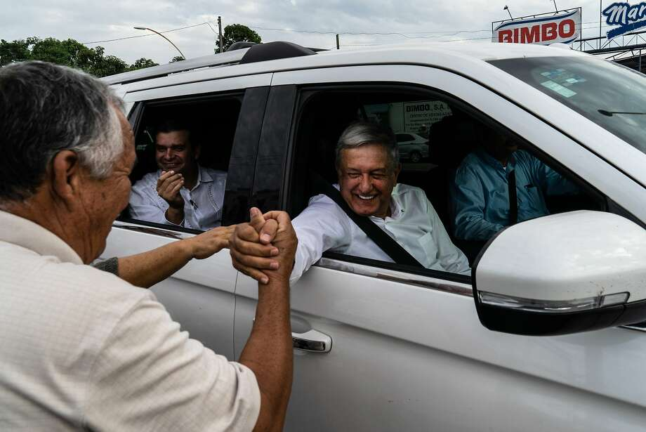 Andres Manual Lopez Obrador, Mexico's president, right, greets attendees after a rally while visiting flood zone victims of Hurricane Willa in the town of Acaponeta, Nyarit state, Mexico, on Friday, Dec. 7, 2018.  CONTINUE to see the world's largest refineries. Photo: Cesar Rodriguez, Bloomberg