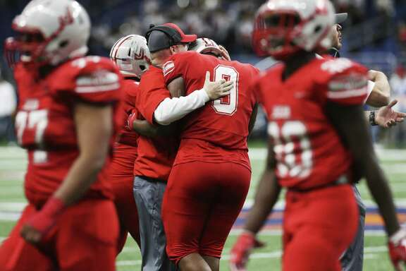 Judson head coach Sean McAuliffe consoles DeMarvin Leal (09) in the closing moments of the game against Austin Lake Travis in the Region IV-6A Division I final game at the Alamodome on Saturday, Dec. 8, 2018. The Rockets ended their playoff run with a 38-21 loss to Lake Travis. (Kin Man Hui/San Antonio Express-News)