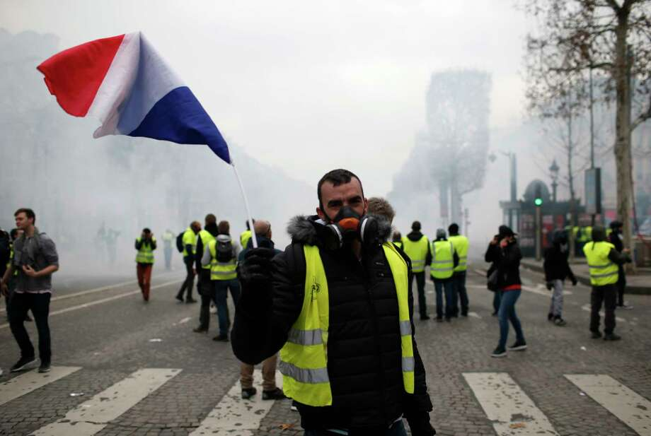 A demonstrator waves a French flag on the Champs-Elysees avenue Saturday, Dec. 8, 2018 in Paris. Crowds of yellow-vested protesters angry at President Emmanuel Macron and France's high taxes tried to converge on the presidential palace Saturday, some scuffling with police firing tear gas, amid exceptional security measures aimed at preventing a repeat of last week's rioting. (AP Photo/Rafael Yaghobzadeh) Photo: Rafael Yaghobzadeh / Copyright 2018 The Associated Press. All rights reserved.