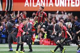 Atlanta United's Josef Martinez leaps in the air and Miguel Almiron charges the field celebrating winning the MLS Cup 2-0 over the Portland Timbers on Saturday, Dec 8, 2018, in Atlanta. (Curtis Compton/Atlanta Journal-Constitution/TNS)