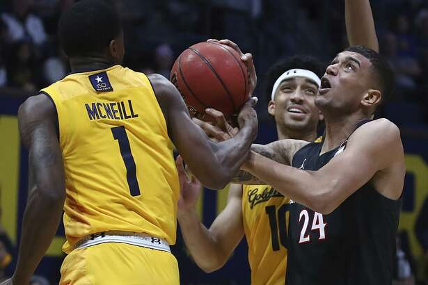 The Aztecs' Nolan Narain (24) shoots between Cal's Darius McNeill (left) and Justice Sueing in the first half at Haas Pavilion.