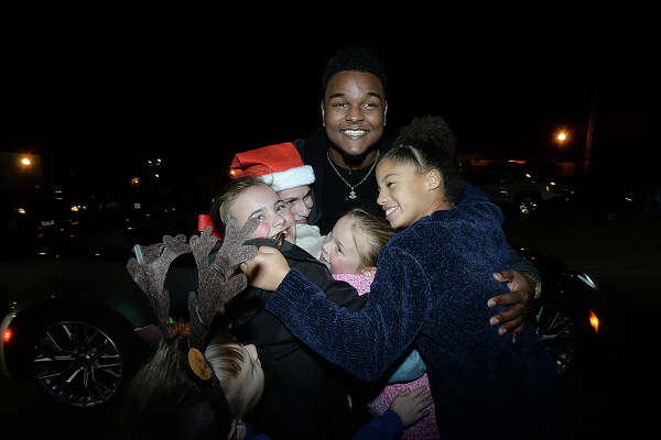 """Deandre Nico, who was recently a contestant on """"The Voice,"""" and was grand marshal of the City of Port Arthur's annual lighted Holiday Parade, stops to hug and take pictures with fans as he makes his way down Procter Street. Photo taken Saturday, December 8, 2018 Kim Brent/The Enterprise"""