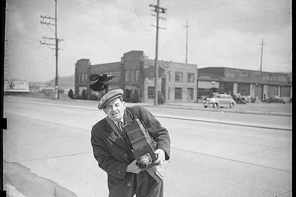 Photographer Art French being attacked by blackbird, Seattle, 1943