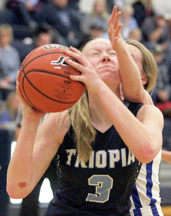 Triopia's Hannah Werries is fouled by a North Greene player during Saturday's 39-29 Triopia victory in White Hall. Photo: Dennis Mathes, Journal-Courier | For The Telegraph