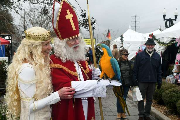 "Wim Wijnberg, center, of Houston, performing as ""Sinterklaas"", with Wendy Crowe, left, of Youngstown, OH., performing as the ""Golden Angel"", visit for a photo with Tiki Macaw, who belongs to Robert Hamann, of The Woodlands, during Tomball's 11th German Christmas Market at the Depot Plaza in Tomball on Dec. 8, 2018."