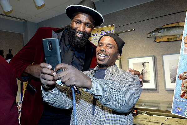 Kendrick Perkins poses for a picture with fan Ron Lyons during the induction ceremony into the Sports Hall of Fame at the Museum of the Gulf Coast Saturday. Family, friends and fans packed the auditorium for the event, in which the 2003 Ozen graduate and Earl Evans of Lincoln High School's class of 1974 were both honored. Both went on from prominent high school careers to playing in the NBA. Photo taken Saturday, December 8, 2018 Kim Brent/The Enterprise