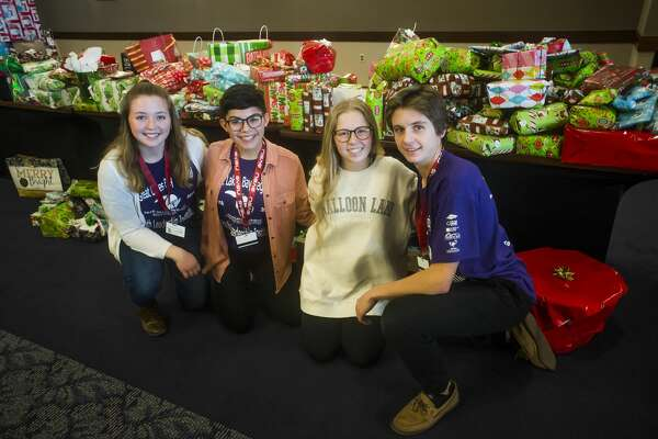 From left, Meridian senior Taryn Weisenberger, Bullock Creek senior Lydia Church, Dow junior Grace Baillargeon and Dow junior Alec Newton pose for a photo in front of gifts they helped to wrap that will be donated to regional nonprofits as part of Saginaw Valley State University'€™sGreat Lakes Bay Regional Youth Leadership Institute on Friday, Dec. 7, 2018 at SVSU. (Katy Kildee/kkildee@mdn.net)