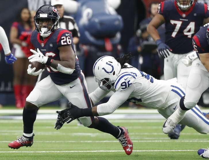 Houston Texans running back Lamar Miller (26) is brought down by Indianapolis Colts defensive tackle Denico Autry (96) on a short reception during the second quarter of an NFL football game at NRG Stadium on Sunday, Dec. 9, 2018, in Houston.
