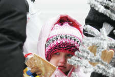 A bundled-up Lylah Blurton, 4, of Greenville, hands over an item she is purchasing at the Edwardsville Winter Market Saturday. Customers braved temperatures in the mid- to lower-20s to shop for a variety of goods. The market is sponsored by the Edwardsville Parks and Recreation Department.