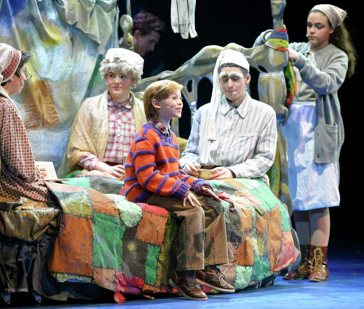 Charlie Bucket, center, played by Turn of River seventh-grader Leo Field, sits on the couch with the Bucket family in the Stamford All-School Musical performance of