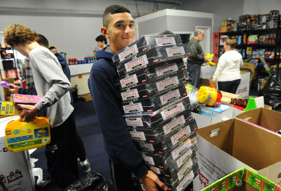 Nathaniel Collazo, of Ansonia, and his Notre Dame of Fairfield baseball teammates sort toys for Greater Bridgeport Christian Fellowship's Toys for Tots drive at 180 Boston Ave. in Bridgeport on Sunday. The church recently suffered a major theft of more than 800 toys from four storage pods, but has been receiving generous donations for their toy distribution next weekend. Photo: Brian A. Pounds / Hearst Connecticut Media / Connecticut Post
