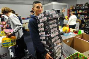 Nathaniel Collazo, of Ansonia, and his Notre Dame of Fairfield baseball teammates sort toys for Greater Bridgeport Christian Fellowship's Toys for Tots drive at 180 Boston Avenue in Bridgeport, Conn. on Sunday, December 9, 2018. The church recently suffered a major theft of over eight hundred toys from four storage pods, but has been receiving generous donations for their toy distribution next weekend.
