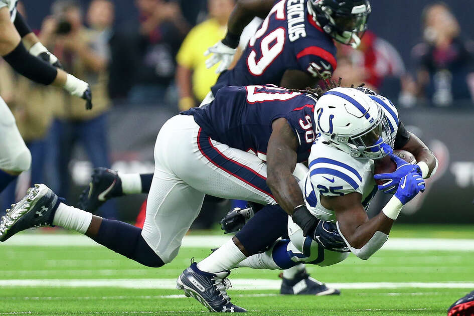 Houston Texans outside linebacker Jadeveon Clowney (90) tackles Indianapolis Colts running back Marlon Mack (25) during the third quarter of an NFL game at NRG Stadium Sunday, Dec. 9, 2018, in Houston. The Colts won 24-21.