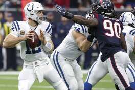Indianapolis Colts quarterback Andrew Luck (12) dodges the outstretched arm of Houston Texans outside linebacker Jadeveon Clowney (90) during the first quarter of an NFL football game at NRG Stadium on Sunday, Dec. 9, 2018, in Houston.
