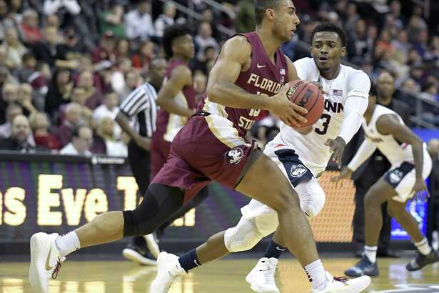 Florida State guard Anthony Polite is pressured by UConn's Alterique Gilbert during Saturday's game.