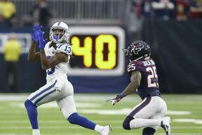 T.Y. Hilton (13) of the Indianapolis Colts catches a pass as he slips behind Kareem Jackson (25) of the Houston Texans during the fourth quarter at NRG Stadium on December 9, 2018 in Houston, Texas.
