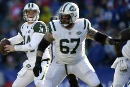New York Jets quarterback Sam Darnold looks for a receiver behind the block of guard Brian Winters (67) during the first half of an NFL football game against the Buffalo Bills, Sunday, Dec. 9, 2018, in Orchard Park, N.Y. (AP Photo/Adrian Kraus)