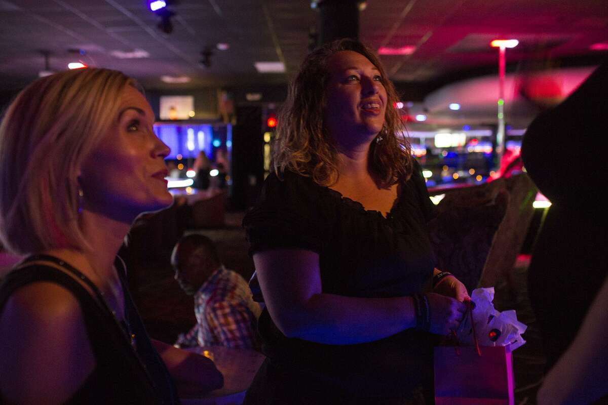 Lisa Michelle, left, founder of No Strings Attached, and volunteer Brook Singh, center, talk with a dancer at a strip club in San Antonio.