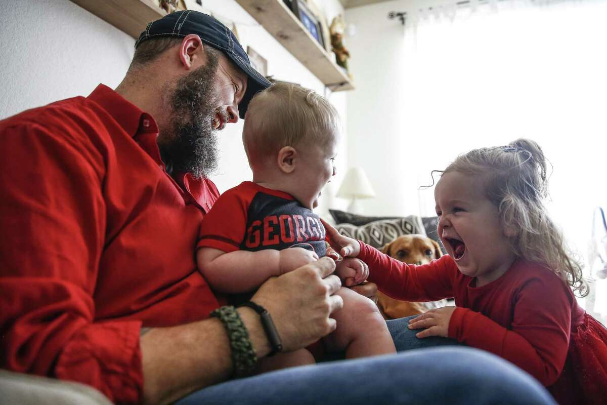 Dillon Bright laughs as Charlotte Bright, 2, right, tickles her nine-month-old brother, Mason Bright, Saturday, Nov. 3, 2018, in Tomball. Child Protective Services was hit with $127,000 in sanctions after improperly removing the Bright's children from their home after Mason fell and fractured his skull when he was five months old.