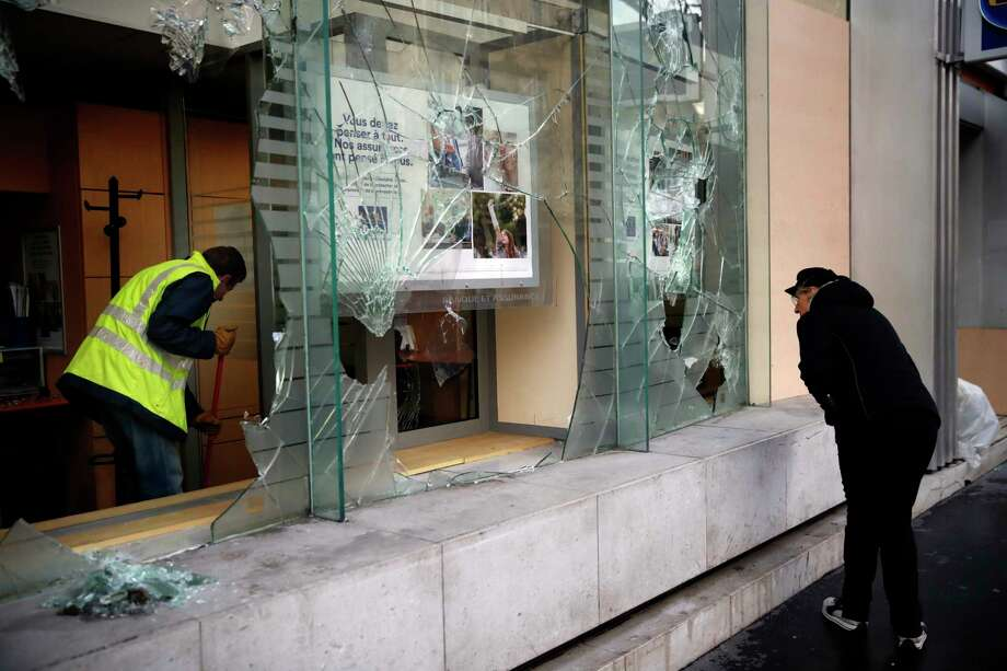 A worker clears debris in a bank as a man watches through smashed windows, in Paris, Sunday, Dec. 9, 2018. Paris monuments reopened, cleanup workers cleared debris and shop owners tried to put the city on its feet again Sunday, after running battles between yellow-vested protesters and riot police left 71 injured and caused widespread damage to the French capital. (AP Photo/Christophe Ena) Photo: Christophe Ena / Copyright 2018 The Associated Press. All rights reserved.