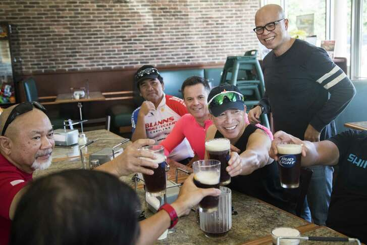 Jonathan Coz, center, 60, surrounded by members of the Siklista-Houston Cycling Club, raise their beer glasses honoring the birthday of one of their members Saturday at a pizzeria in Richmond, Dec. 1, 2018, after the group returned from their weekly cycling ride. Coz, a long time marathoner and cyclist suffered a heart attack, his doctor Konstantinos Charitakis, sitting behind him, inserted multiple stents to reopen Coz's artery, during his recovery the pair discovered their common interest in cycling.