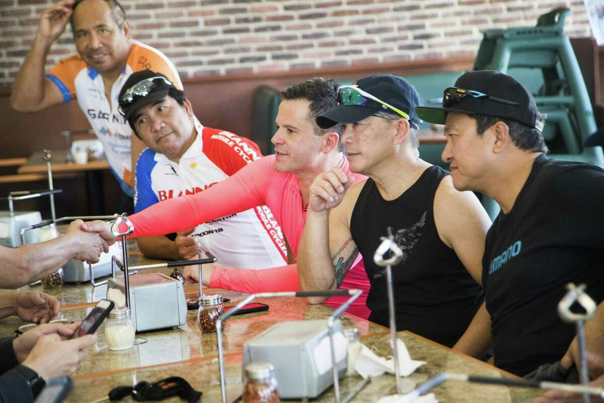 Konstantinos Charitakis, an assistant professor of medicine and cardiovascular disease specialist shakes hands with members of the Siklista-Houston Cycling Club, as the group gathers Saturday morning in Richmond after a cycling ride, Dec. 1, 2018.