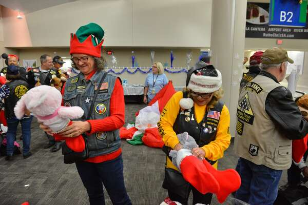 Lisa Menard and Margie Delatorre stuff stockings for children taking the Snowball Express Saturday morning at the San Antonio International Airport as part of the Gary Sinise Foundation to Disneyland
