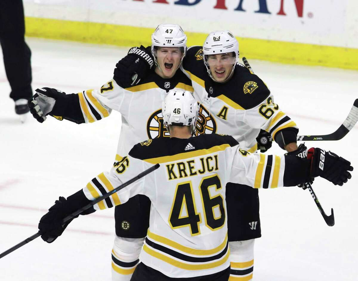 Boston Bruin defenseman Torey Krug (47) celebrates his winning overtime goal with teammates Brad Marchand (63) and David Krejci (46) at the end of NHL hockey overtime action against the Ottawa Senators, in Ottawa, Sunday, Dec. 9, 2018. (Fred Chartrand/The Canadian Press via AP)