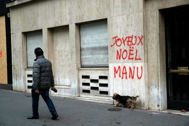 A man walks his dog past a tag reading : Happy Christmas Manu, referring to French President Emmanuel Macron, in Paris, Sunday, Dec. 9, 2018. Paris monuments reopened, cleanup workers cleared debris and shop owners tried to put the city on its feet again Sunday, after running battles between yellow-vested protesters and riot police left 71 injured and caused widespread damage to the French capital.