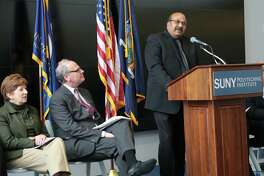 "Omkaram ""Om"" Nalamasu, the chief technology officer at Applied Materials, speaks during an announcement back in November. Seated next to him is Howard Zemsky, CEO of Empire State Development, and Albany Mayor Kathy Sheehan."