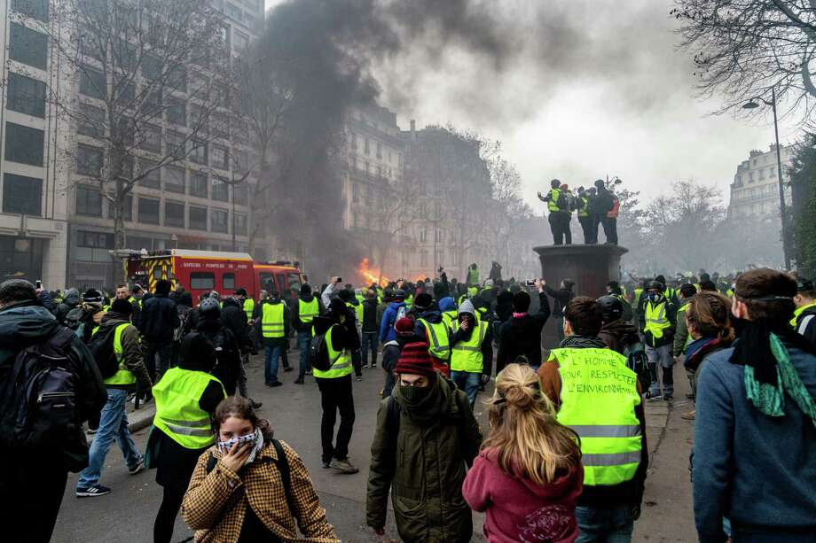 Demonstrators wearing yellow vests protest as a vehicle burns in Paris on Dec. 8, 2018. Photo: Bloomberg Photo By Anita Pouchard Serra. / © 2018 Bloomberg Finance LP