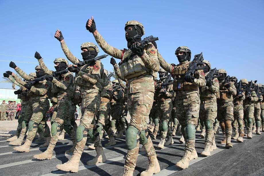"Members of Iraq's Rapid Response military unit parade during a ceremony at a military base inside Baghdad's International Airport, marking the first anniversary of the country's victory over the Islamic State (IS) group, on December 10, 2018. - A year since Iraq announced ""victory"" over the Islamic State group, the country finds itself in the throes of political and economic crises left unresolved during the long battle against jihadists. (Photo by AHMAD AL-RUBAYE / AFP)AHMAD AL-RUBAYE/AFP/Getty Images Photo: AHMAD AL-RUBAYE;Ahmad Al-rubaye / AFP / Getty Images"