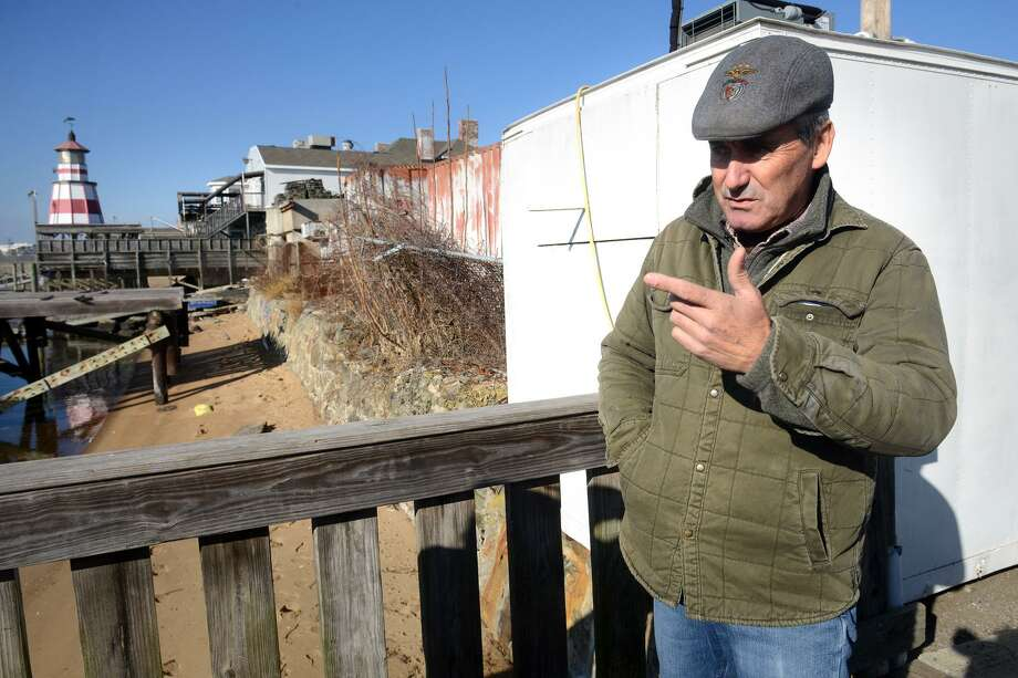Joe Henriques, owner of H&H Shellfish, stands on one of his docks as he describes how he and his workers found the body of a woman on the small beach, seen here to the left, early Sunday morning in Bridgeport, Conn., Dec. 10, 2018. On Monday Bridgeport identified the victim as 25-year-old Emily Todd, of Bethel, and confirmed that she died from a bullet wound to the head. Photo: Ned Gerard / Hearst Connecticut Media / Connecticut Post