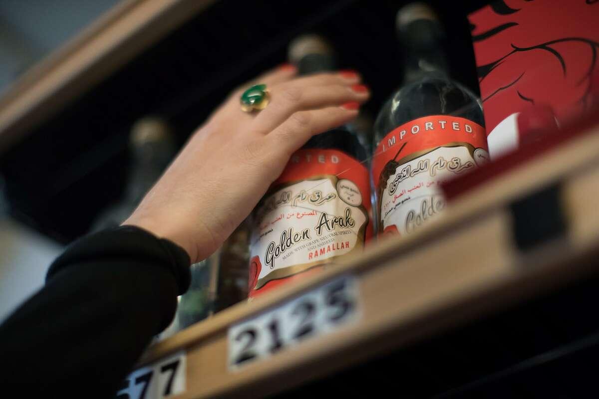 Miriam Zouzounis shelves a bottle of Ramallah Golden Arak, the most popular Palestinian arak.