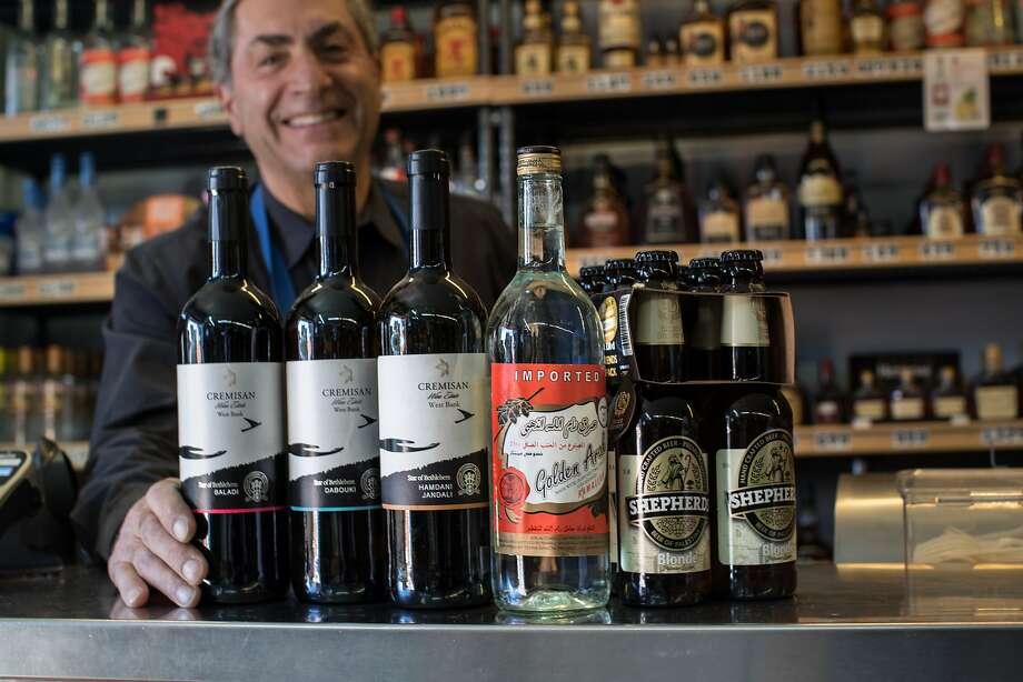 Owner David Zouzounis displays bottles of Palestinian beverages imported by Terra Sancta: Cremisan Cellars Star of Bethlehem Wines, Arak Ramallah, Shepherd's Beer. Photo: Paul Kuroda / Special To The Chronicle