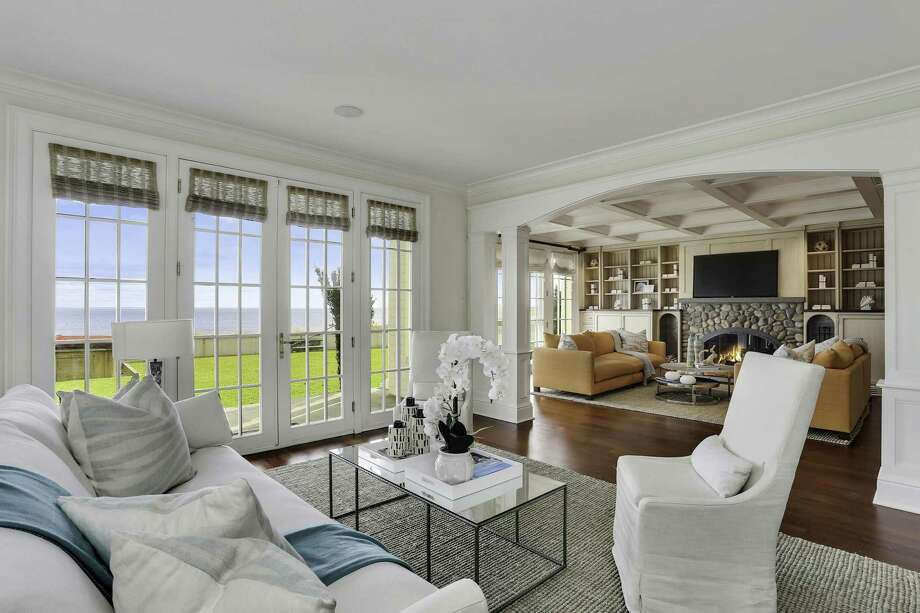 The living room at 1640-1641 Fairfield Beach Road opens to a great room with a coffered ceiling, a stone fireplace and Brazilian cherry floors. Photo: William Raveis Real Estate / ONLINE_CHECK
