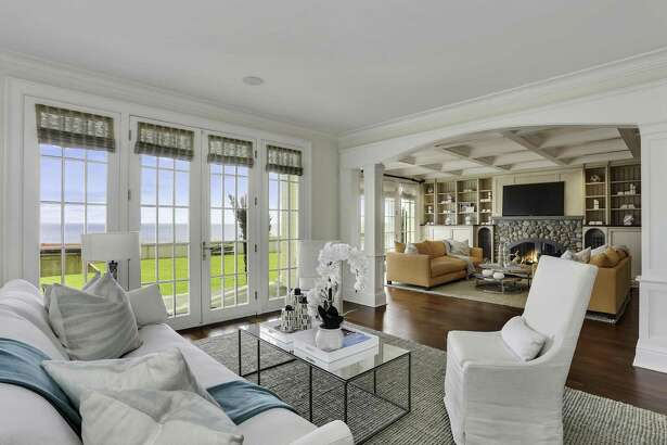 The living room at 1640-1641 Fairfield Beach Road opens to a great room with a coffered ceiling, a stone fireplace and Brazilian cherry floors.