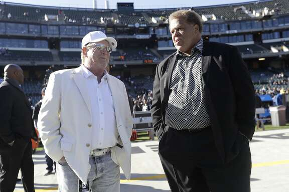 FILE - In this Dec. 24, 2016, file photo, Oakland Raiders owner Mark Davis, left, talks with general manager Reggie McKenzie before an NFL football game between the Raiders and the Indianapolis Colts, in Oakland, Calif. The Raiders have fired general manager Reggie McKenzie less than two years after he was named the NFL's executive of the year. A person familiar with the move says McKenzie was let go on Monday, Dec. 10, 2018, from the position he had held for almost seven seasons. The person spoke on condition of anonymity because the team has not made an announcement. (AP Photo/Marcio Jose Sanchez, File)