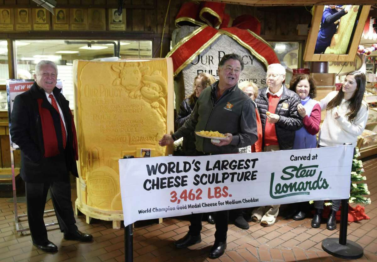 """Norwalk Mayor Harry Rilling, left, joins President and CEO Stew Leonard Jr., center, and the rest of the Leonard family to unveil a 3,462 pound carved block of cheddar cheese at Stew Leonard's grocery store in Norwalk, Conn. Monday, Dec. 10, 2018. Norwalk Mayor Harry Rilling joined the Stew Leonard family to unveil the soon-to-be Guinness Book of World Records' largest cheese sculpture. The mammoth cheddar sculpture has carved into it the longtime Stew Leonard's customer service motto from its """"Customer Service Rock of Commitment."""" More than 500 cows contributed milk to the record breaking cheese, which was carved in East Meadow, N.Y."""